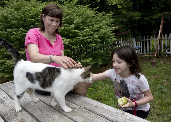 Abby Howard and her daughter, Kristen, play with their cat at her home in Gilsum, N.H., Thursday, July 7, 2016. When Howard decided to seek a restraining order against her husband in 2012, she had no legal help to navigate the civil court system. Her husband, meanwhile, hired a lawyer who helped him lower his monthly child support payments and file for a divorce. The mother of four with a part-time job, felt outsmarted and unsure how to best advocate for her and her children. She eventually found a lawyer through New Hampshire Legal Assistance, a nonprofit that provides free services to low-income victims. (AP Photo/Jim Cole)